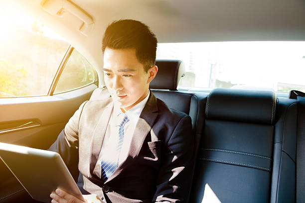 young businessman using tablet pc in car at morning stock photo