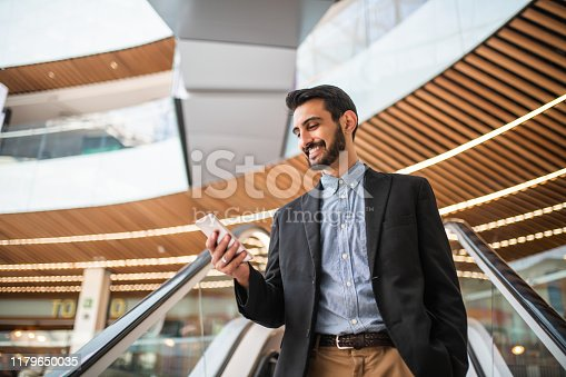 Young businessman using the smartphone on the escalator. Getting information before a meeting is important