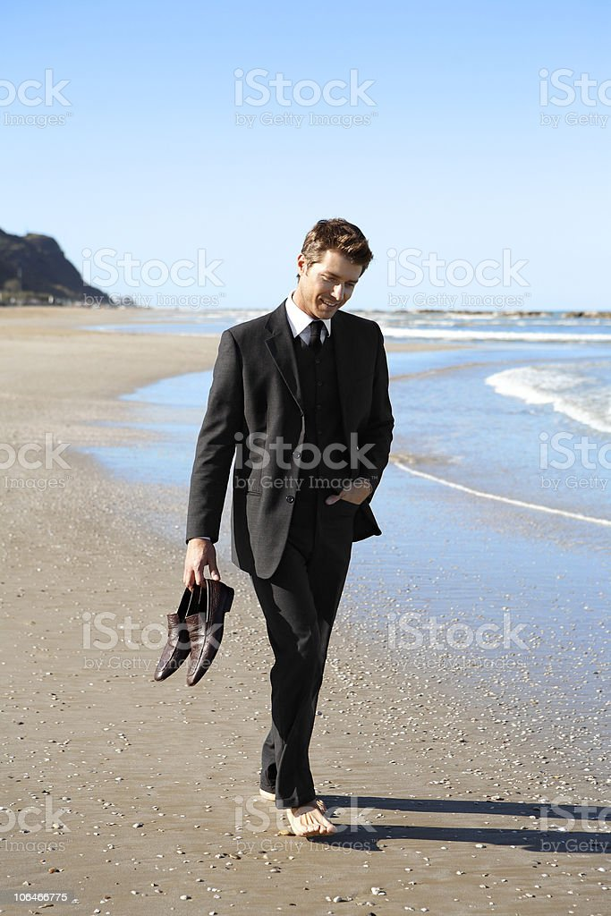 Young businessman walking barefoot on beach stock photo