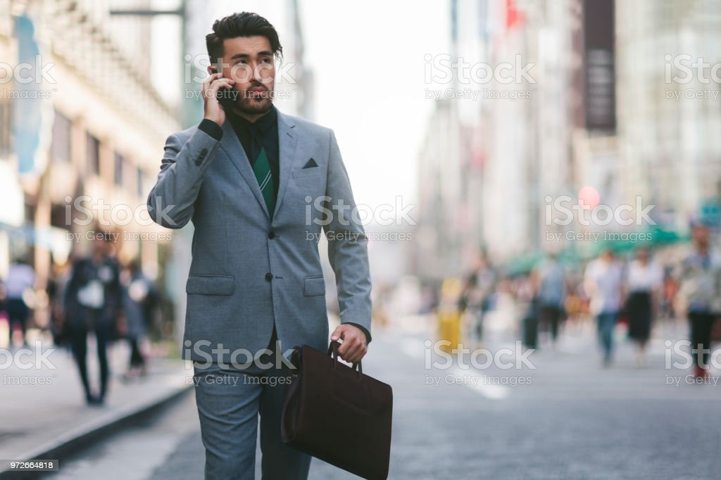 A young Japanese businessman is walking in the street in Tokyo while...