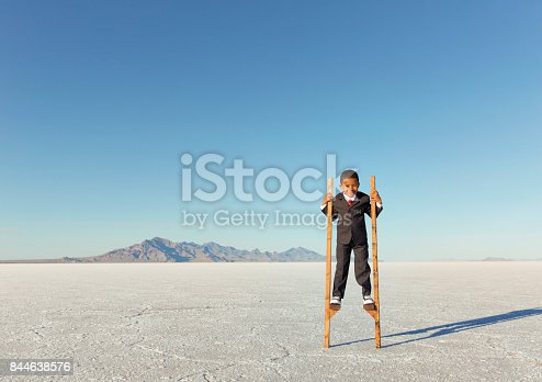 istock Young Businessman Walking on Stilts 844638576