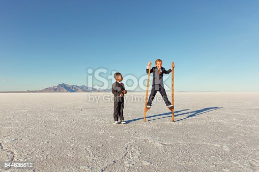844638658 istock photo Young Businessman Walking on Stilts 844638612
