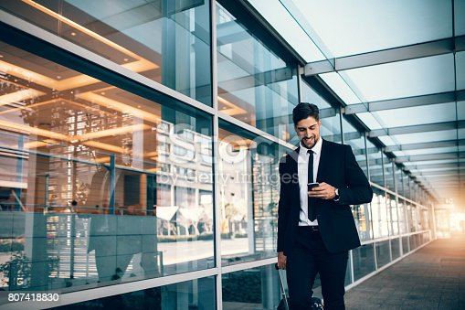 Happy young businessman walking and looking at mobile phone at airport. Handsome business executive texting on smartphone while walking outside airport terminal.
