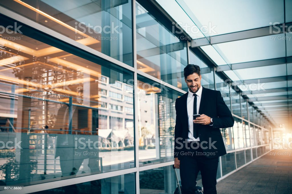 Young businessman walking with mobile phone at airport stock photo