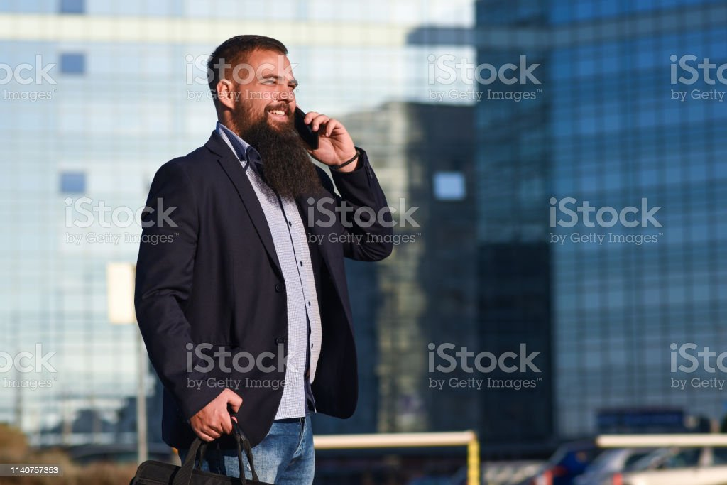 Young businessman walking with mobile phone