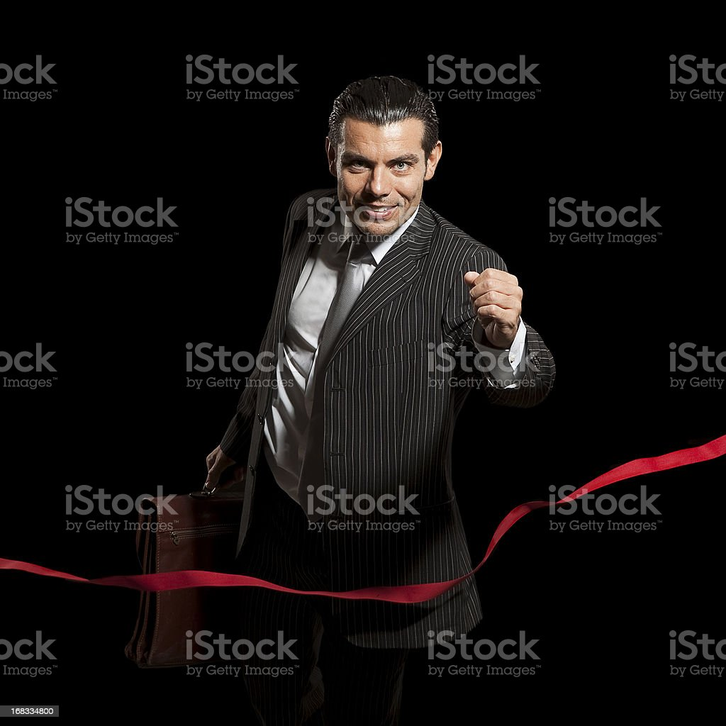 Young businessman winning race on finish line royalty-free stock photo