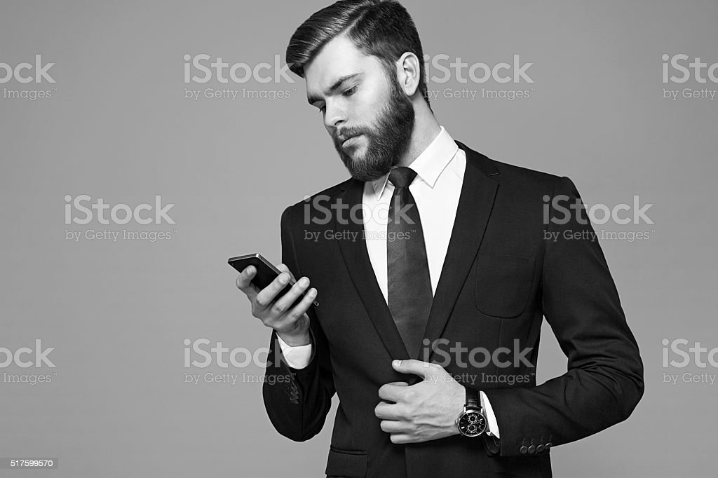 Young businessman with a beard holding a phone stock photo