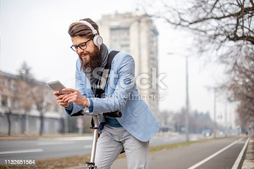 istock Young businessman with a beard on kick scooter 1132651564