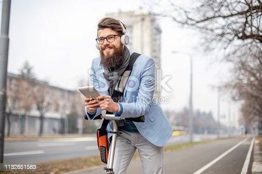 istock Young businessman with a beard on kick scooter 1132651583