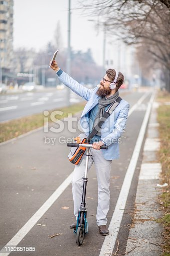 istock Young businessman with a beard on kick scooter 1132651585