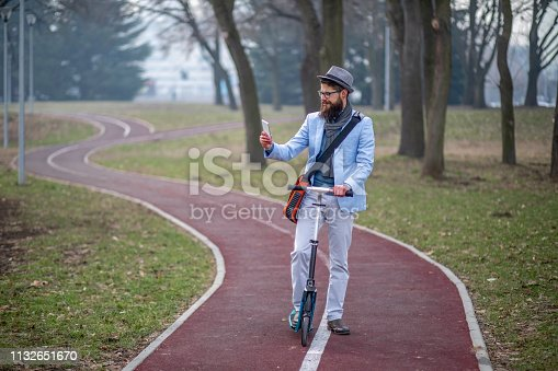 istock Young businessman with a beard on kick scooter 1132651670