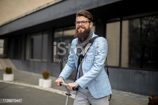 istock Young businessman with a beard smiling on kick scooter 1129070447