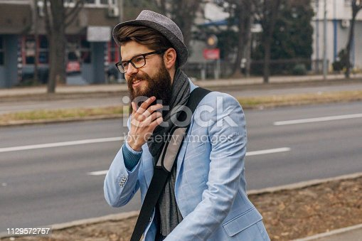 istock Young businessman with a beard smiling on kick scooter 1129572757