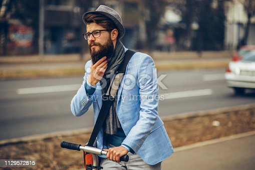 istock Young businessman with a beard smiling on kick scooter 1129572815