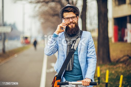 istock Young businessman with a beard smiling on kick scooter 1129572909