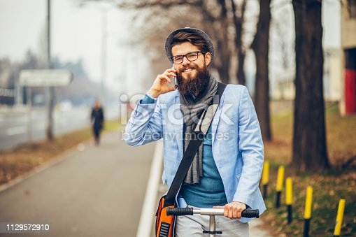 istock Young businessman with a beard smiling on kick scooter 1129572910