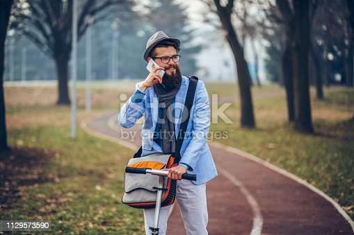 istock Young businessman with a beard smiling on kick scooter 1129573590