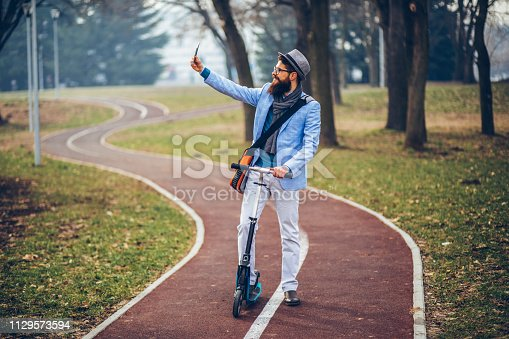 istock Young businessman with a beard smiling on kick scooter 1129573594
