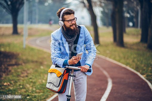 istock Young businessman with a beard smiling on kick scooter 1129573656