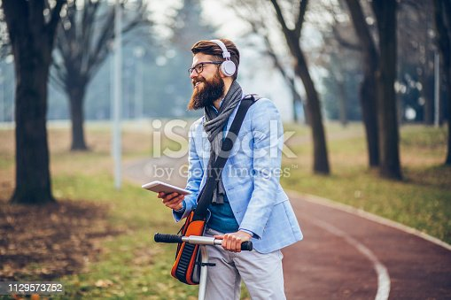 istock Young businessman with a beard smiling on kick scooter 1129573752