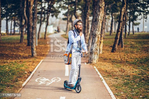 istock Young businessman with a beard smiling on kick scooter 1129573753