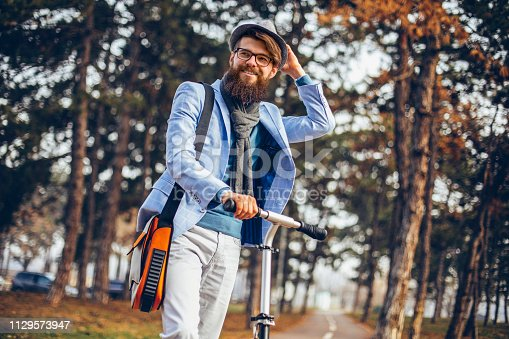istock Young businessman with a beard smiling on kick scooter 1129573947