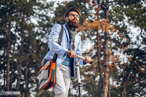 istock Young businessman with a beard smiling on kick scooter 1129573958
