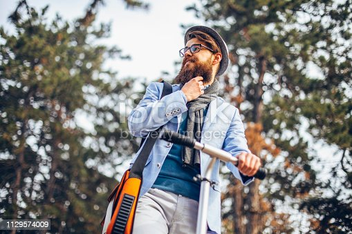 istock Young businessman with a beard smiling on kick scooter 1129574009