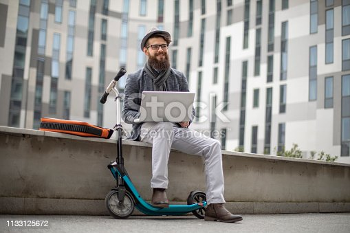 istock Young businessman with a beard smiling on kick scooter 1133125672