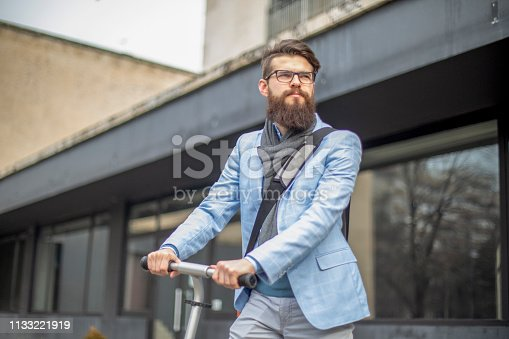 istock Young businessman with a beard smiling on kick scooter 1133221919