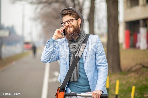 istock Young businessman with a beard smiling on kick scooter 1133221925