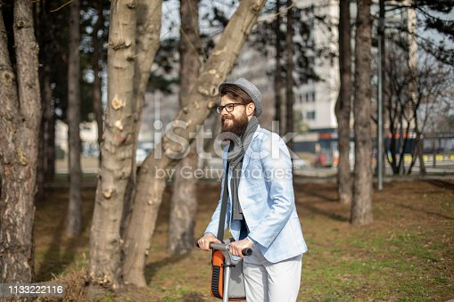 istock Young businessman with a beard smiling on kick scooter 1133222116