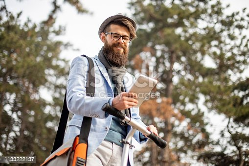 istock Young businessman with a beard smiling on kick scooter 1133222137