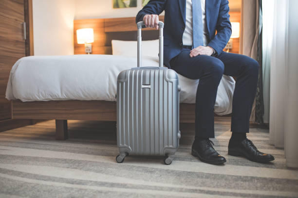 Young businessman with a suitcase in room stock photo