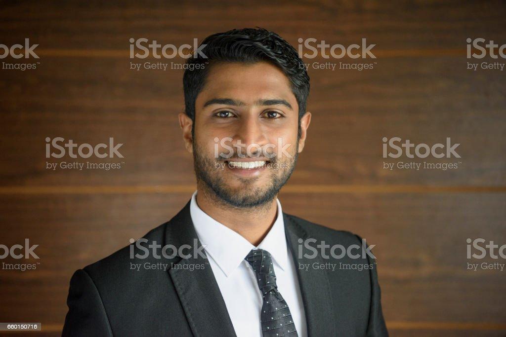 Young businessman with beard smiling towards camera stock photo
