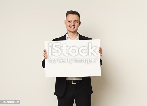 1048561956 istock photo Young businessman with blank white paper 958868596