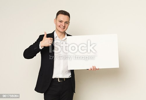 1048561956 istock photo Young businessman with blank white paper 961758084