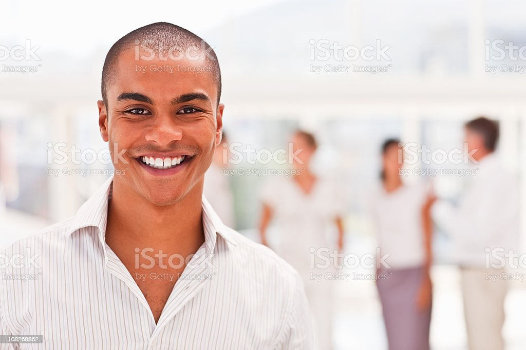 Young businessman with colleagues in the background royalty-free stock photo