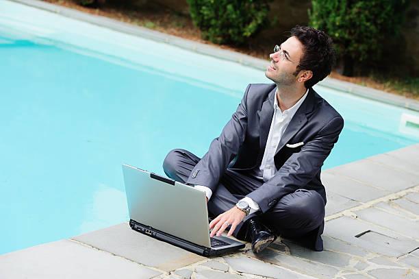 Junger Geschäftsmann mit Computer neben dem Swimmingpool – Foto