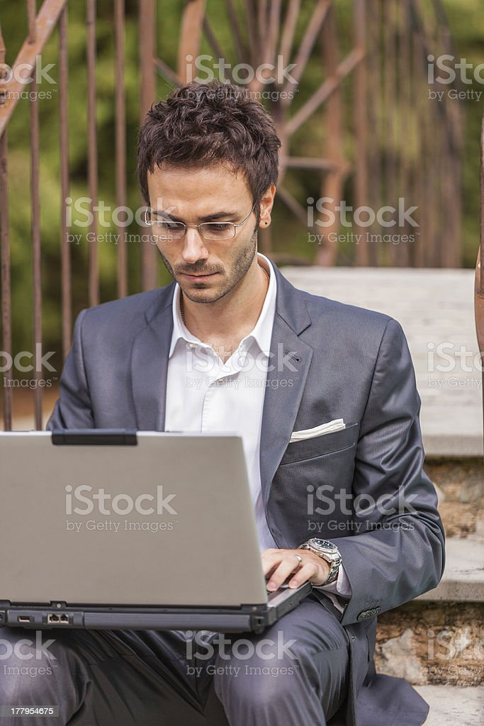 Young Businessman with Computer next to Swimming Pool royalty-free stock photo