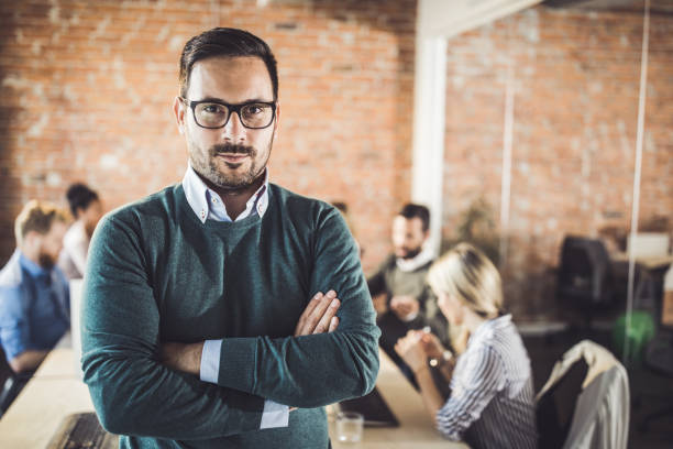 Young businessman with crossed arms at corporate office. stock photo