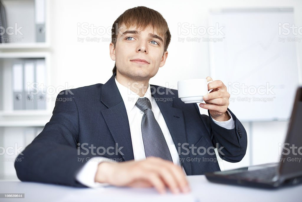 young businessman with cup of coffee in office royalty-free stock photo