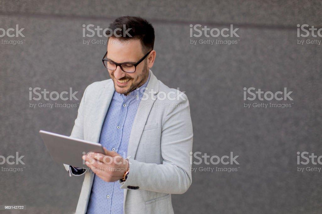 Ung affärsman med digital tablett av den grå väggen - Royaltyfri Affärsman Bildbanksbilder