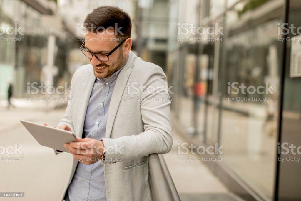 Ung affärsman med digital tablett av kontorsbyggnaden - Royaltyfri Affärsman Bildbanksbilder