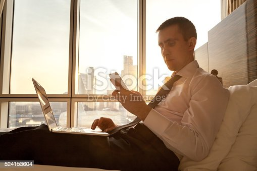 istock Young businessman with electronic devices in hotel 524153604