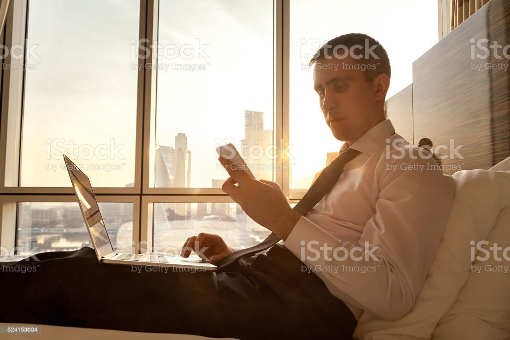 Young businessman with electronic devices in hotel stock photo