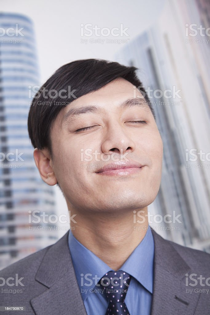 Young businessman with eyes closed and head back smiling, portrait stock photo