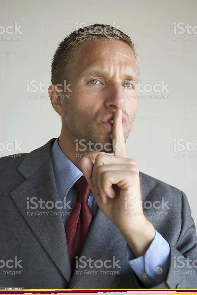 Young businessman with finger against his lips royalty-free stock photo