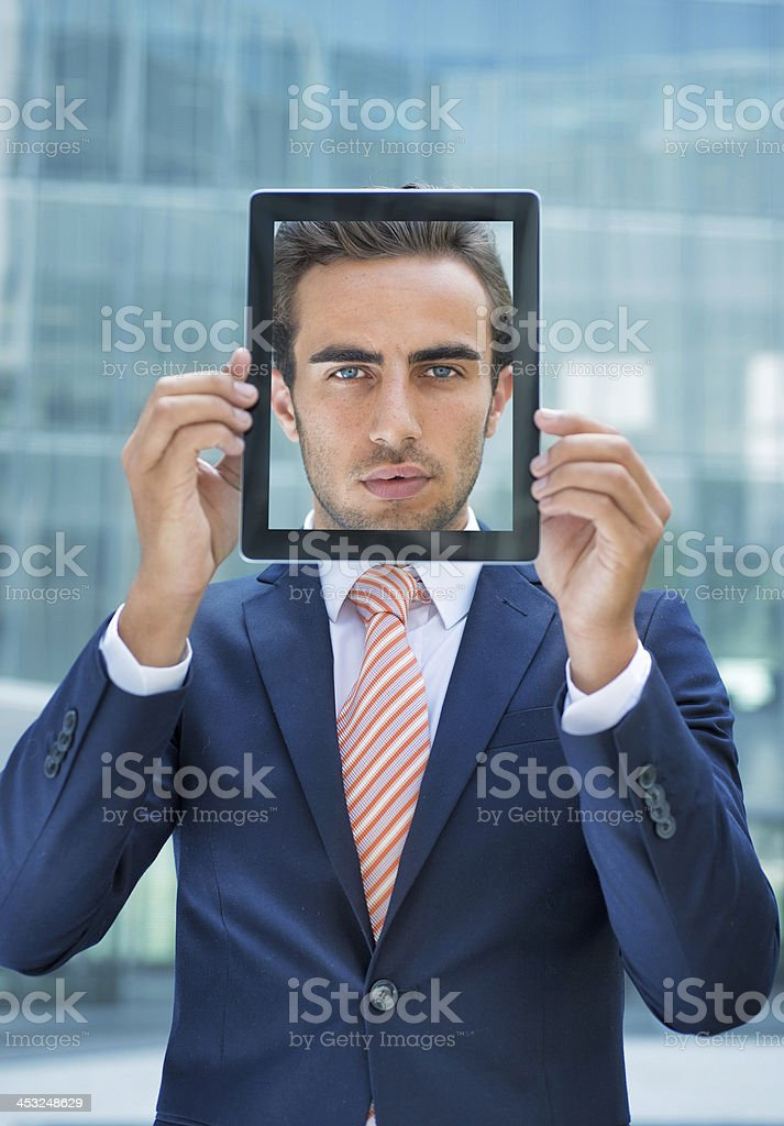 Young Businessman With His Face in a Digital Tablet stock photo