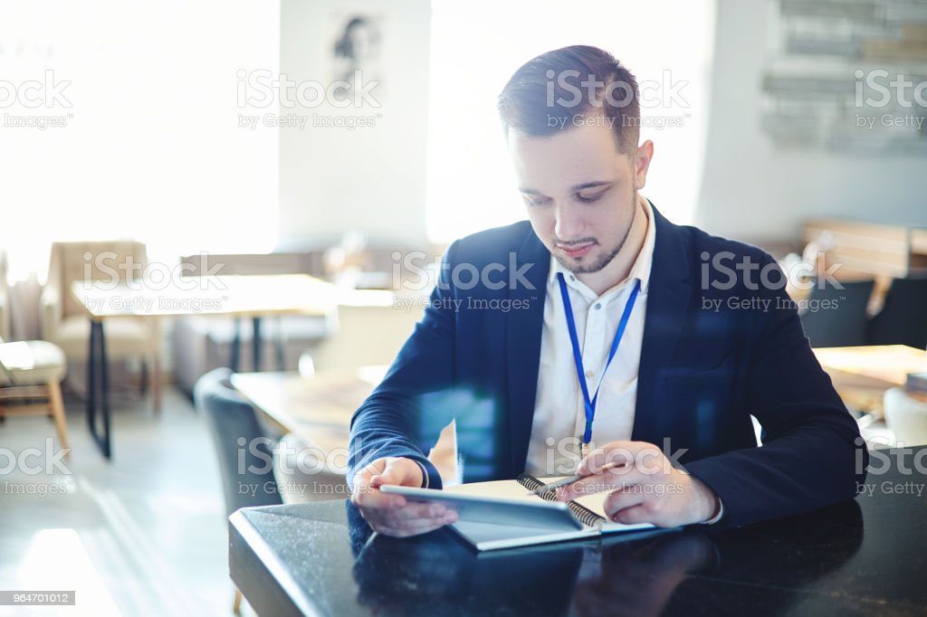 Young businessman with id card around his neck pointing with pen at tablet computer screen while working in coffee break area at conference royalty-free stock photo